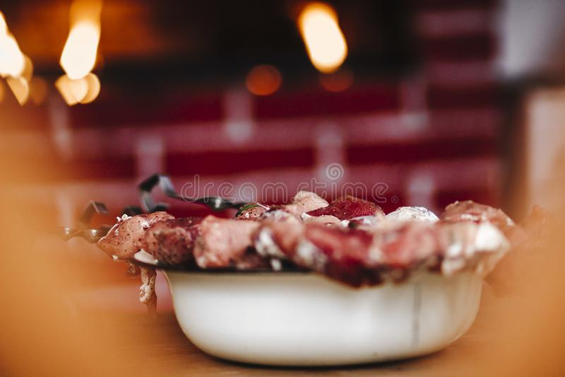 Pork kebab on skewers on the table. Delicious fried pork kebab strung on skewers on the table in the gazebo royalty free stock image