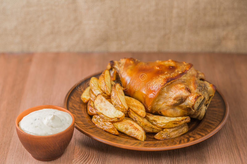 Pork knuckle with potatoes selyanski and garlic sauce. The national dish of Czech cuisine. royalty free stock image