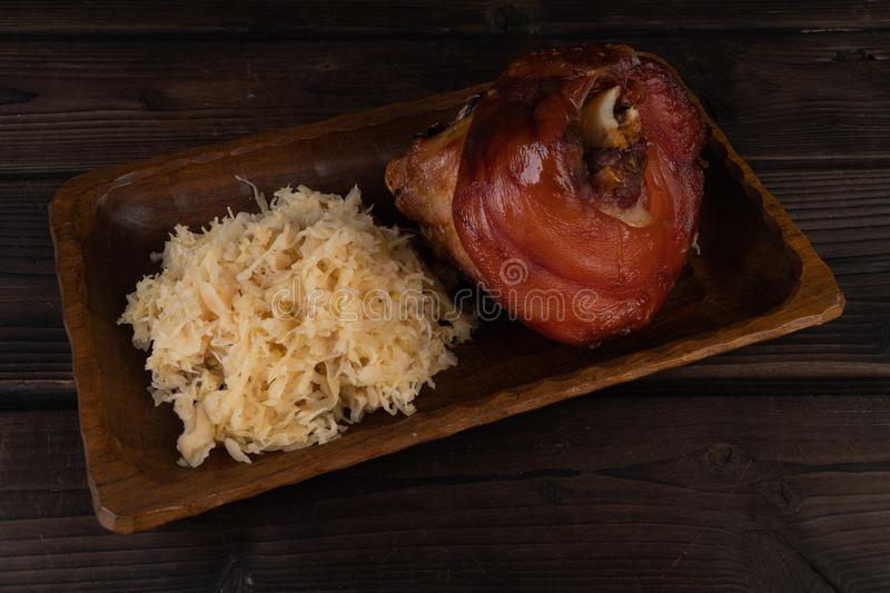 Pork knuckle with sauerkraut on a wooden plate. Oktoberfest. rustic royalty free stock photo