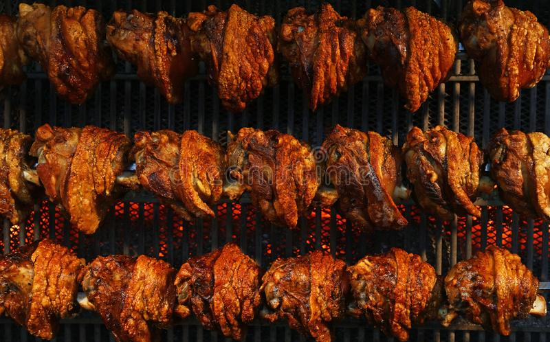 Pork knuckles slowly cooked at rotation grill. Several traditional Bavarian German roasted pork knuckles slowly cooked at rotating broiling rack grill spit royalty free stock photography