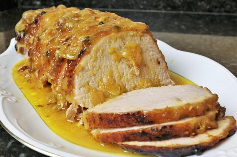 Pork loin meat in orange sauce stock images