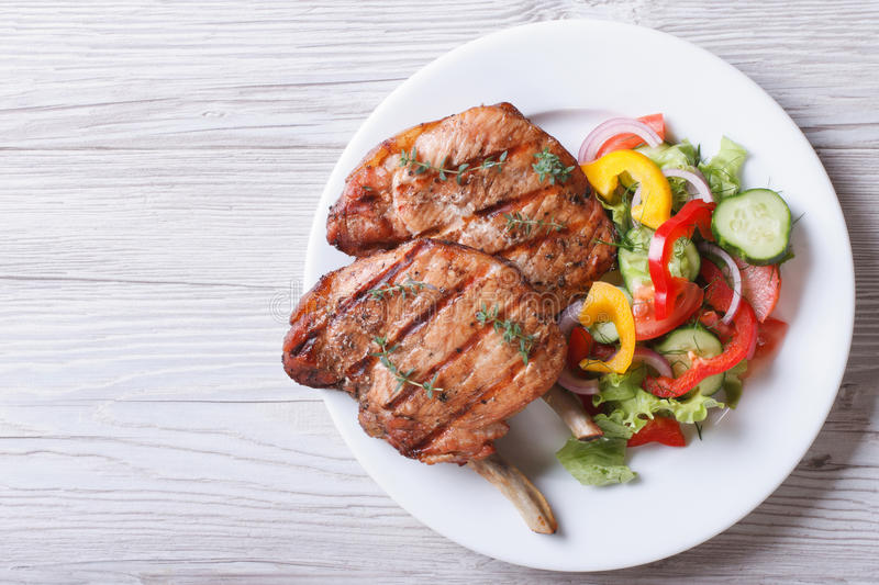 Pork meat grilled with fresh vegetable salad top view stock image
