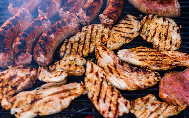 Pork meat and sausages grilled on a charcoal barbeque. Top view of tasty barbecue, food concept, food on grill and detail of food. On the grill stock photo