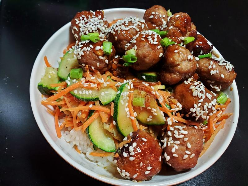 Pork meatballs with carrots, zucchini and rice royalty free stock images