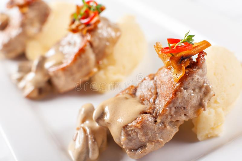 Pork Medallions with Mashed Potato and Mushrooms. Pork tenderloin on a white plate, good serving. restaurant menu stock photo