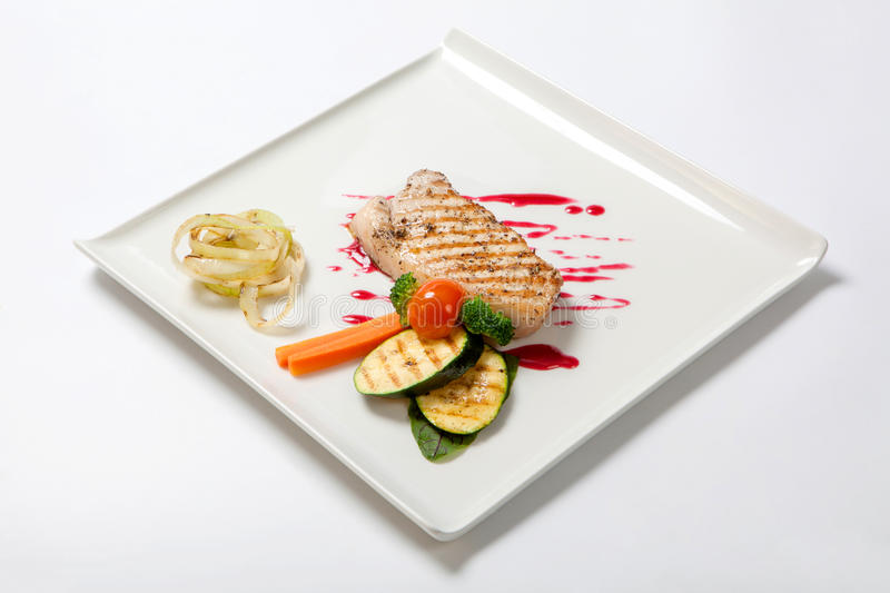Pork medium rare with a side dish of grilled zucchini flavored cranberry sauce royalty free stock photos