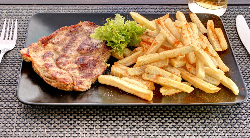 Pork neck with french fries on black plate stock image