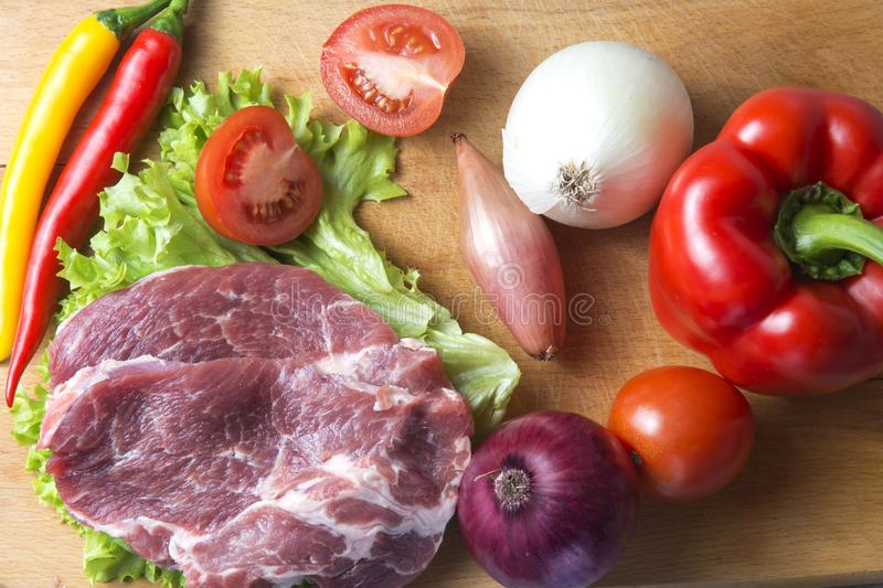 Pork-neck meat steaks on lettuce on the background of radishes, tomato, red chili peppers, yellow chili peppers, green paprika,. Yellow paprika, red paprika stock photography
