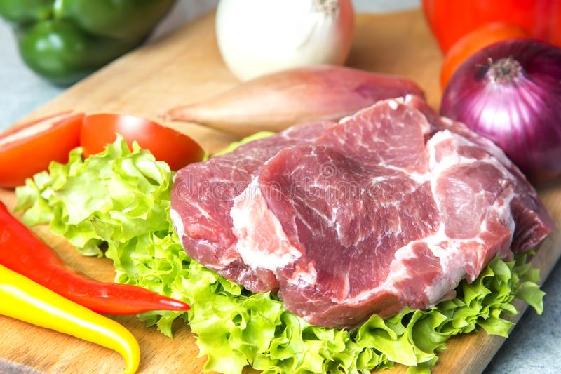 Pork-neck meat steaks on lettuce on the background of radishes, tomato, red chili peppers, yellow chili peppers, green paprika,. Yellow paprika, red paprika stock images