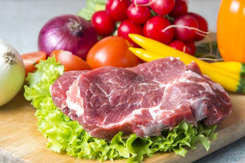 Pork-neck meat steaks on lettuce on the background of radishes, tomato, red chili peppers, yellow chili peppers, green paprika,. Yellow paprika, red paprika stock image