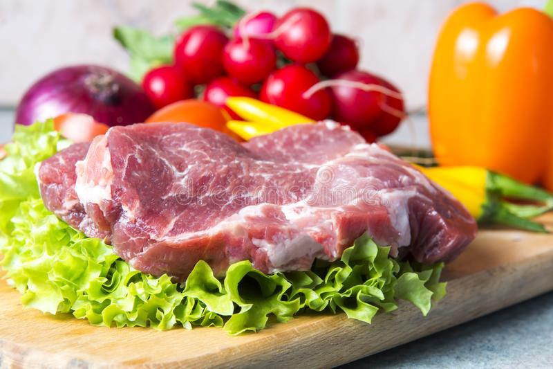Pork-neck meat steaks on lettuce on the background of radishes, tomato, red chili peppers, yellow chili peppers, green paprika,. Yellow paprika, red paprika stock photos