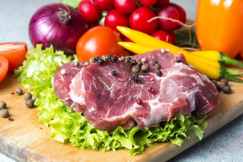 Pork-neck meat steaks on lettuce on the background of radishes, tomato, red chili peppers, yellow chili peppers, green paprika,. Yellow paprika, red paprika stock photo