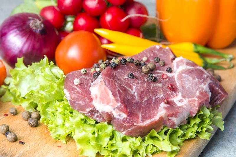 Pork-neck meat steaks on lettuce on the background of radishes, tomato, red chili peppers, yellow chili peppers, green paprika,. Yellow paprika, red paprika royalty free stock photos