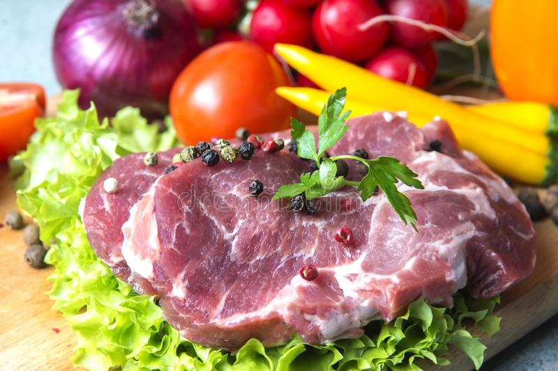 Pork-neck meat steaks on lettuce on the background of radishes, tomato, red chili peppers, yellow chili peppers, green paprika,. Yellow paprika, red paprika royalty free stock images