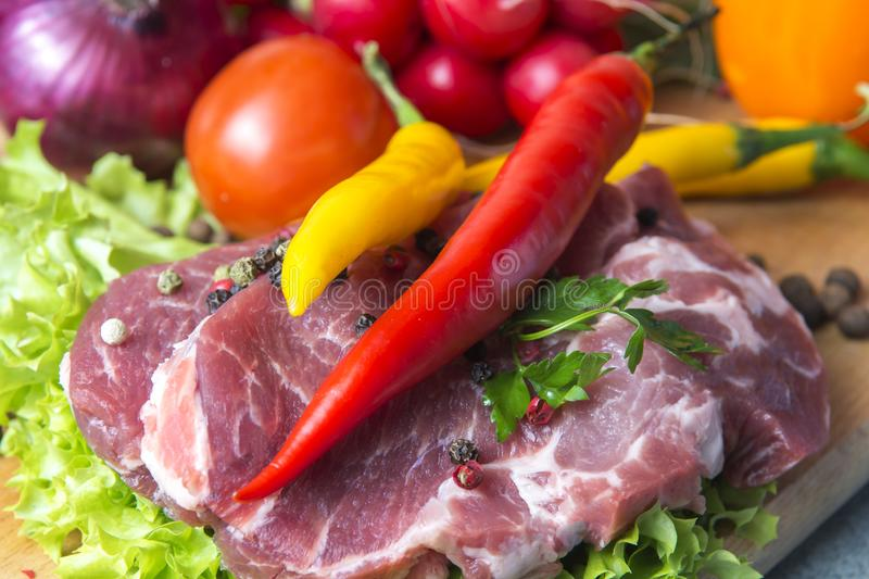 Pork-neck meat steaks on lettuce on the background of radishes, tomato, red chili peppers, yellow chili peppers, green paprika,. Yellow paprika, red paprika royalty free stock photo