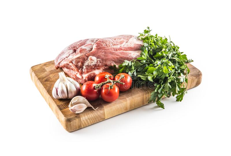 Pork neck raw meat with garlic parsley herbs tomatoes and rosemary on butcher board isolated on white background stock photos