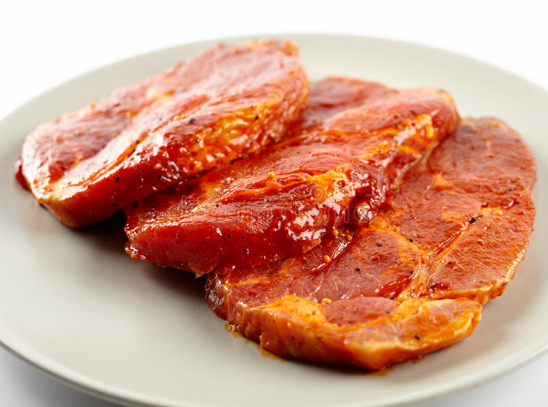 Pork neck slices on a plate. Marinated and seasoned pork neck slices on a plate stock image