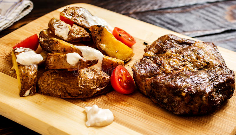 Pork neck steak. Grilled pork neck steak with potatoes on wood table royalty free stock photography