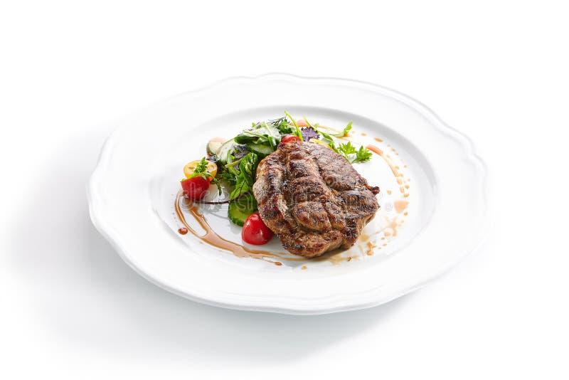 Pork Neck Steak with Mixed Salad on White Restaurent Plate. Macro shot of pork neck steak with mixed salad on white restaurent plate isolated. Restaurant main royalty free stock photos