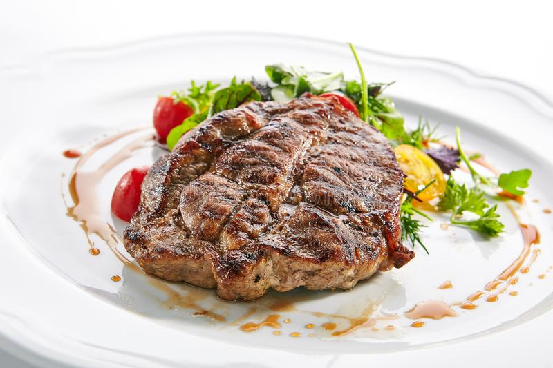 Pork Neck Steak with Mixed Salad on White Restaurent Plate. Macro shot of pork neck steak with mixed salad on white restaurent plate isolated. Restaurant main royalty free stock photography
