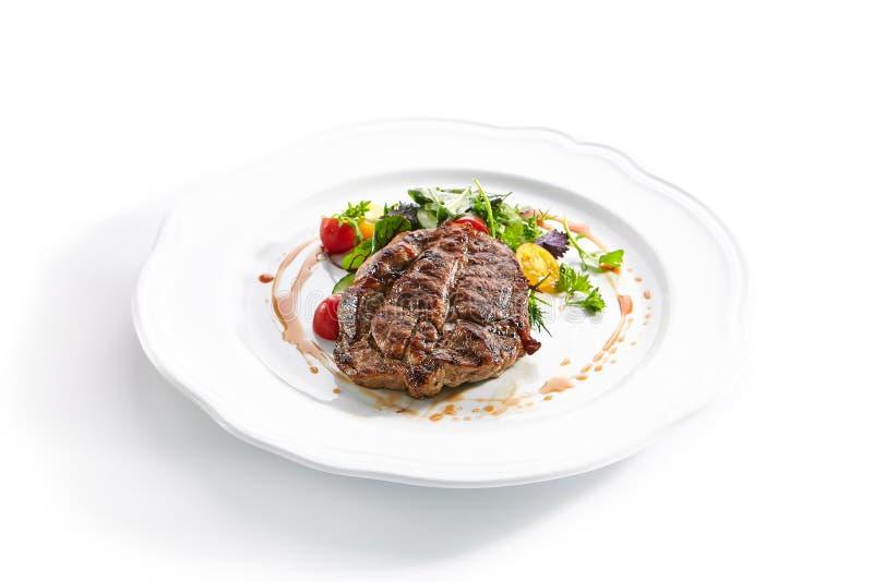 Pork Neck Steak with Mixed Salad on White Restaurent Plate. Macro shot of pork neck steak with mixed salad on white restaurent plate isolated. Restaurant main stock photos