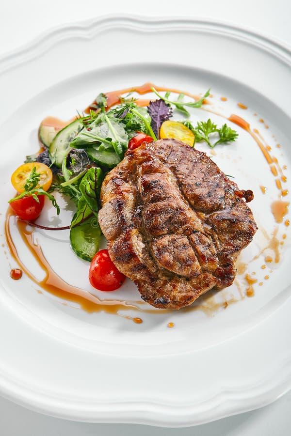 Pork Neck Steak with Mixed Salad on White Restaurent Plate. Top view of pork neck steak with mixed salad on white restaurent plate isolated. Restaurant main stock photos