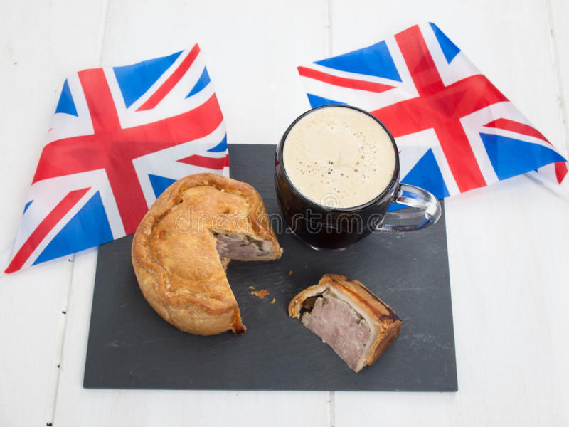 Pork pie and beer with flags. Sliced british pork pie and a half pint of beer on a black slate with rustic white table top behind and union jack flags royalty free stock images