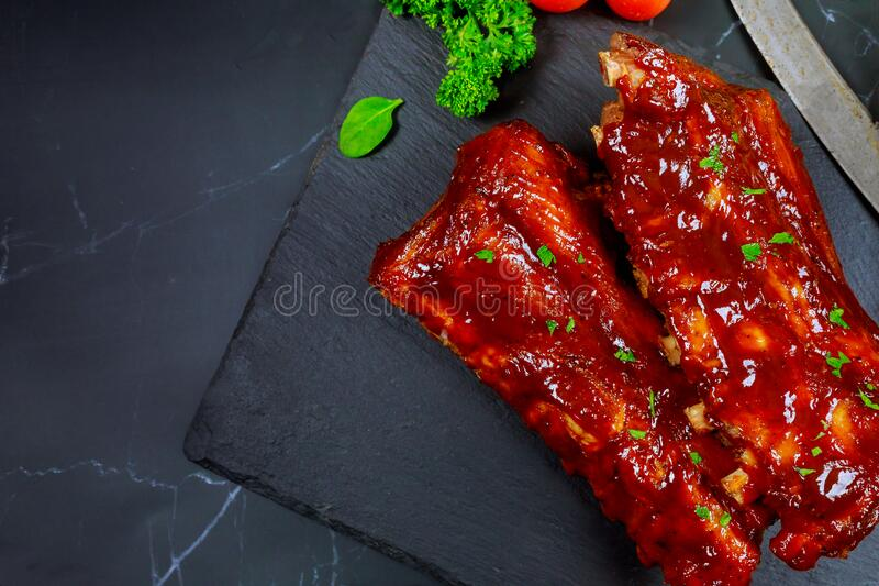 Pork ribs with barbecue sauce on black stone board. Top view stock image