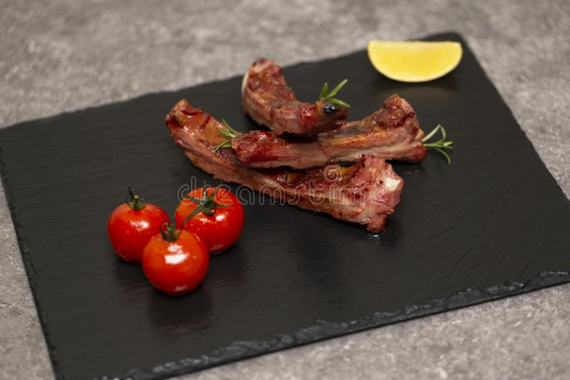 Pork ribs in barbecue sauce and honey roasted tomatoes on a black slate dish. stock photos