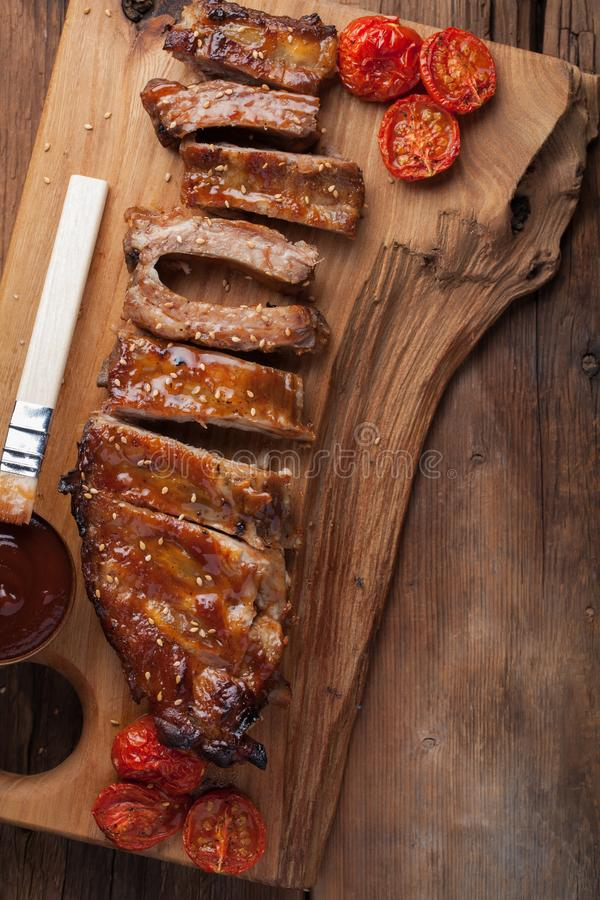 Pork ribs in barbecue sauce and honey roasted tomatoes on a wooden board. A great snack to beer on a rustic wooden table. Top view.  stock photos