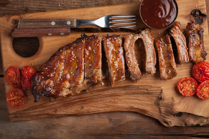 Pork ribs in barbecue sauce and honey roasted tomatoes on a wooden board. A great snack to beer on a rustic wooden table. Top view royalty free stock photography