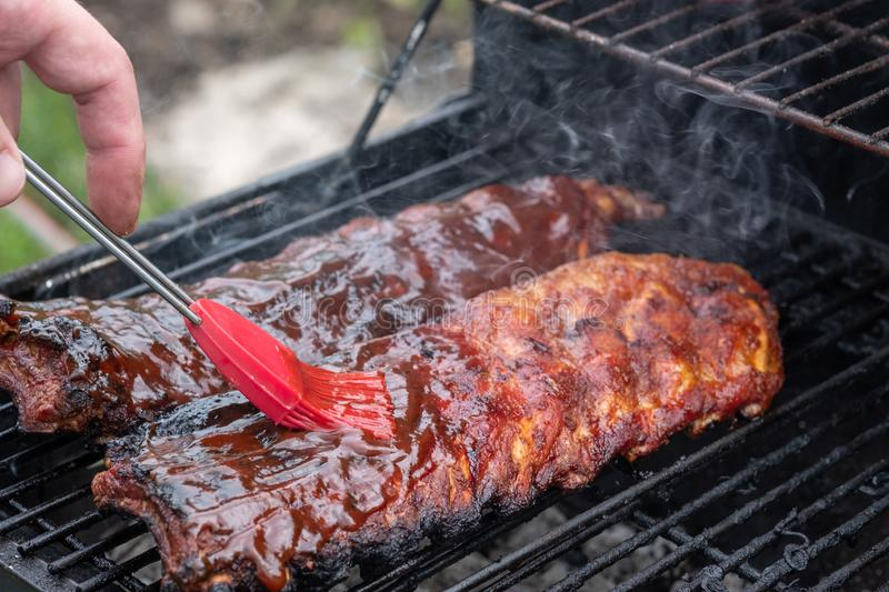 Pork ribs cooking on barbecue grill. For summer outdoor party royalty free stock images