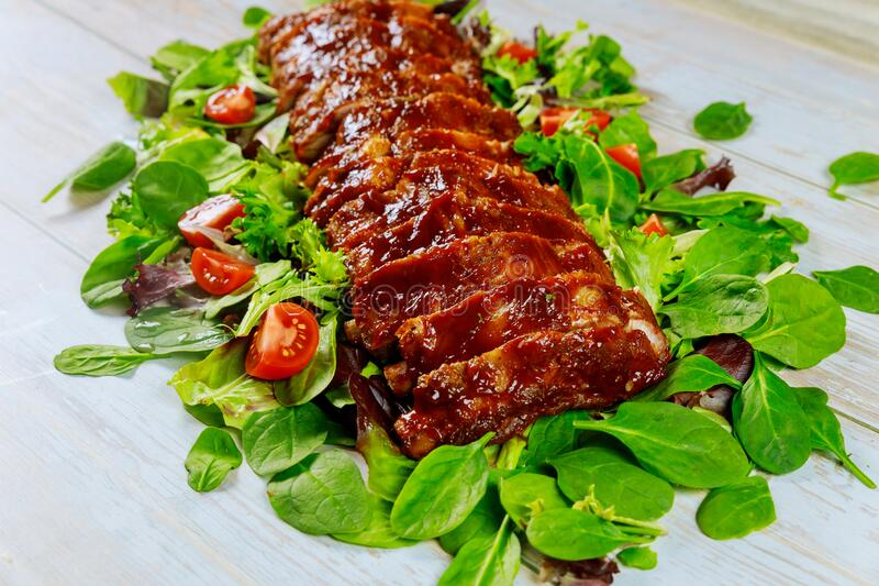 Pork ribs grilled with BBQ sauce , tomato and spinach royalty free stock photo