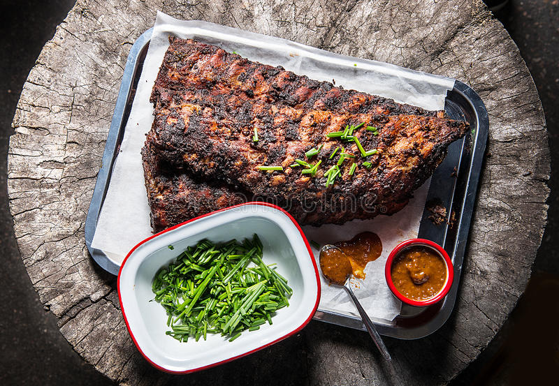 Pork ribs. A grilled pork ribs with chili sauce and chives royalty free stock photo