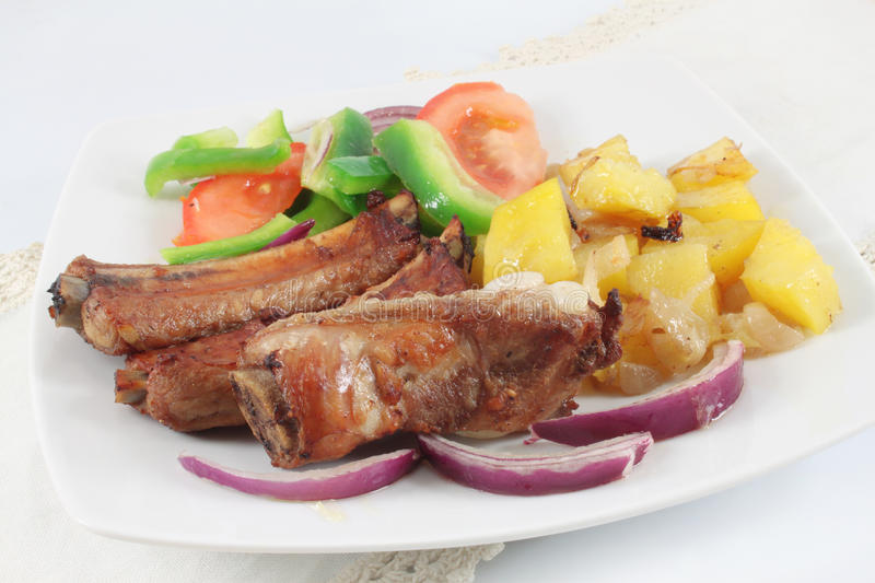 Pork ribs grilled. With potatoes, peppers, tomatoes and onions stock photo
