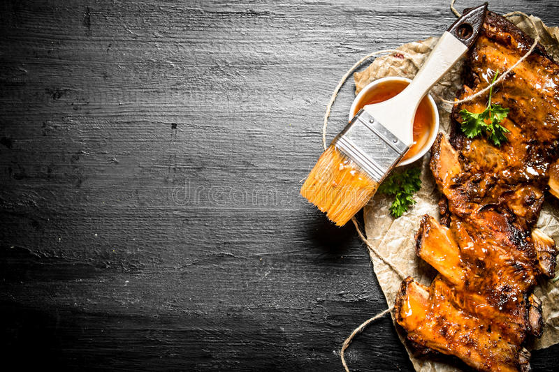 Pork ribs grilled. With a spicy sauce and a brush. On the black chalk Board royalty free stock image