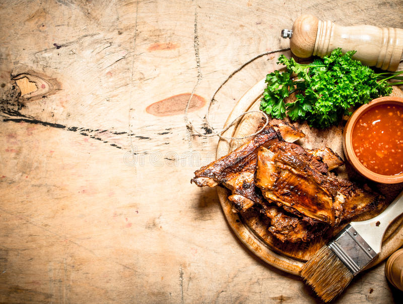 Pork ribs grilled. With a spicy sauce and a brush. On wooden background royalty free stock image