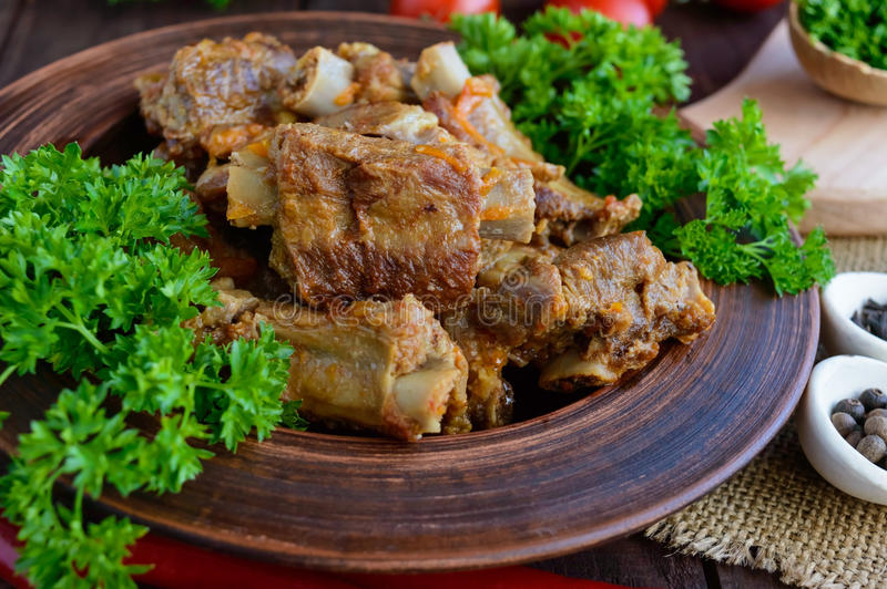 Pork ribs steamed with carrots, parsley decorated in a clay bowl on a wooden background. royalty free stock images