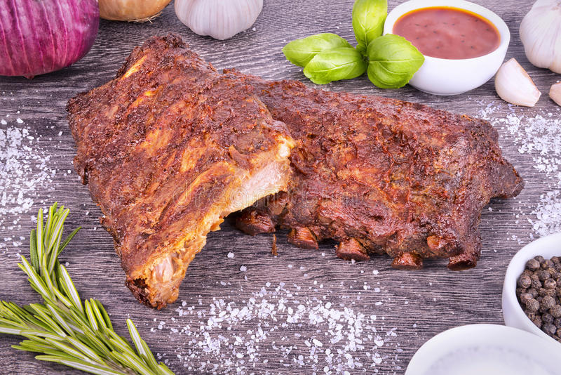Pork ribs. Tasty grilled ribs disposed on wooden plank in background royalty free stock photo