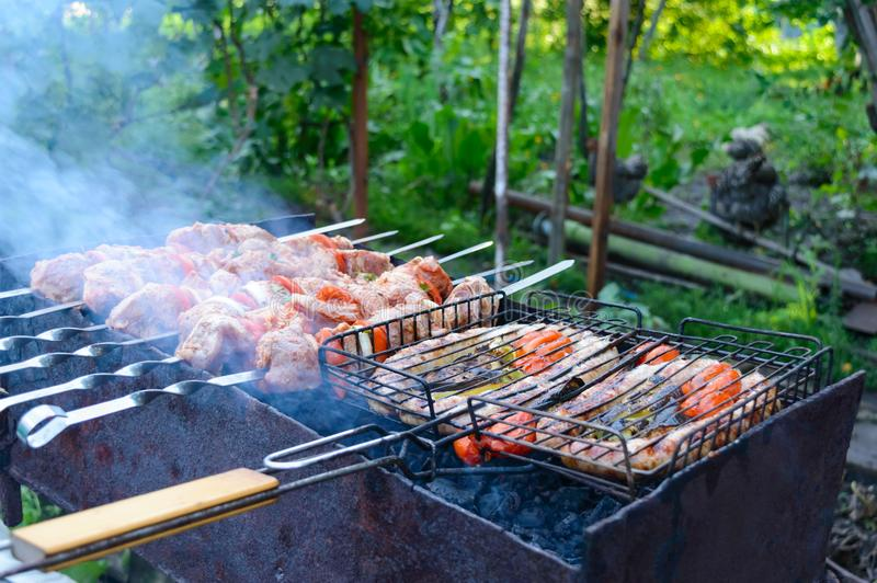 Pork sausages with vegetables and shish kebab are grilled on fire. stock photos