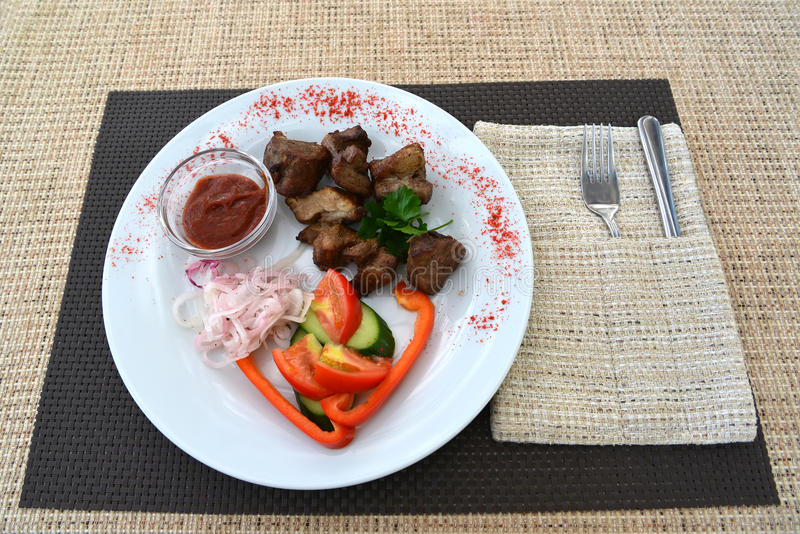 Pork shish kebab with a garnish from fresh vegetables stock photography