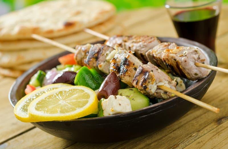 Pork Souvlaki. A delicious grilled pork souvlaki served with greek salad, pita, lemon, and wine stock image