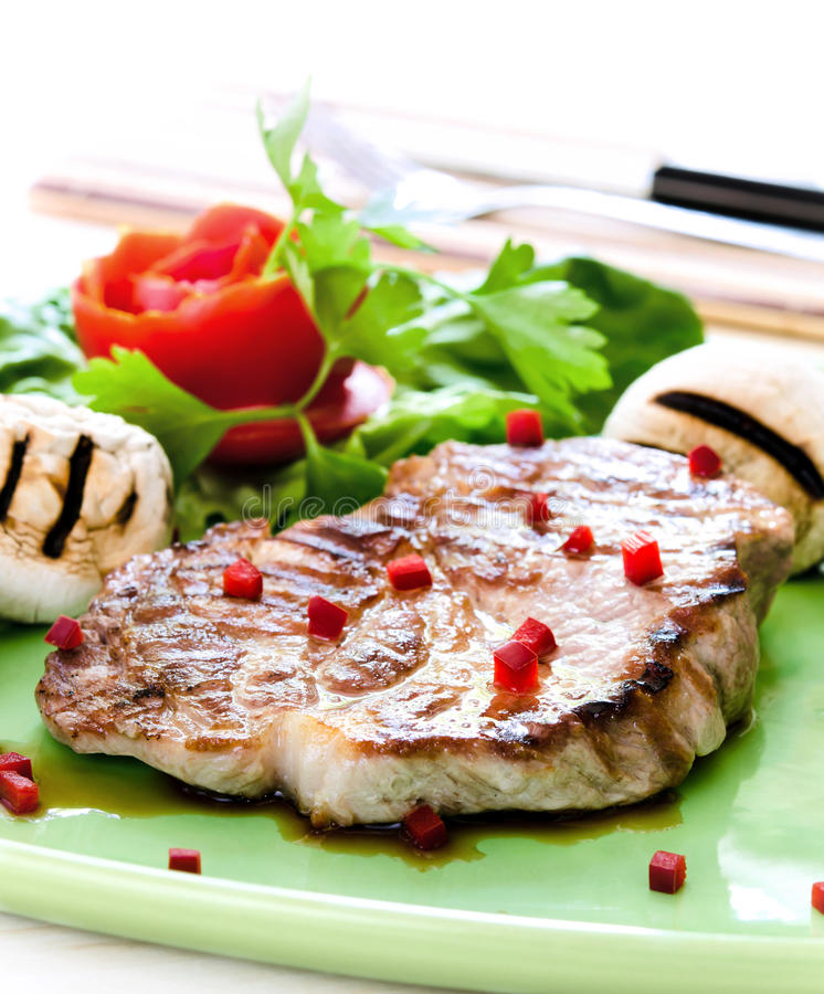 Pork steak. With mushrooms and tomato rose on white background royalty free stock photography