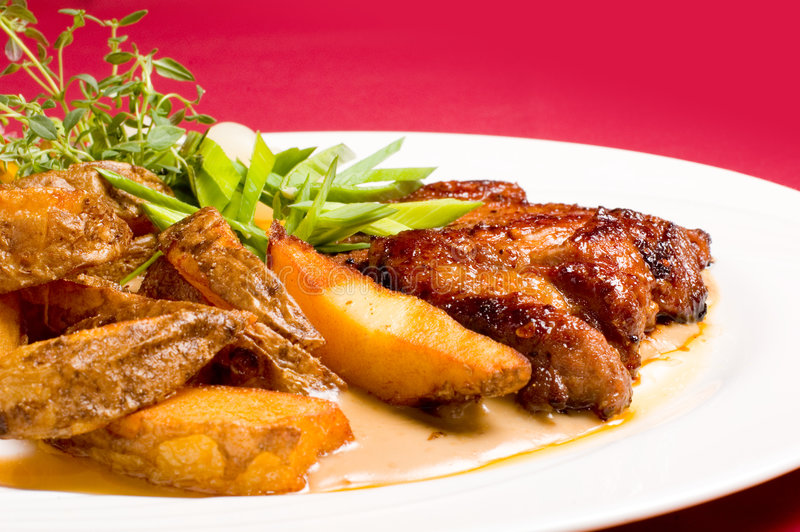 Pork steak with baked potatoes stock image