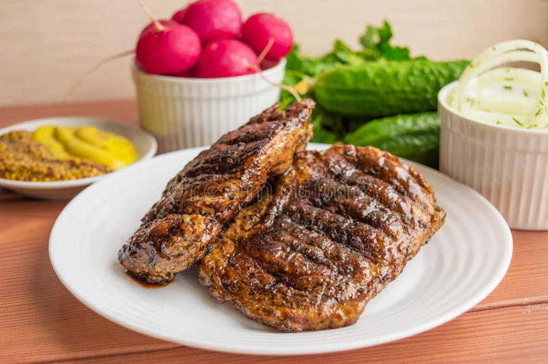 Pork steak, grilled. With onion rings and fresh vegetables, herbs royalty free stock photography
