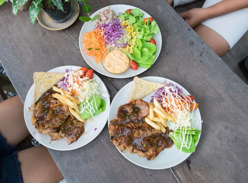 Pork steak with salad tuna on wood table. With friends royalty free stock image