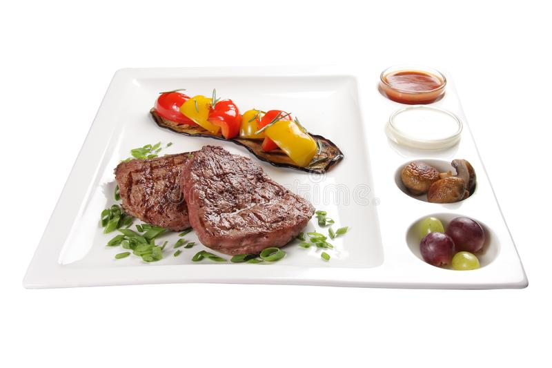 Pork steak with sauces and vegetables. On a white background stock photography