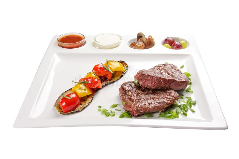 Pork steak with sauces and vegetables. On a white background stock photos