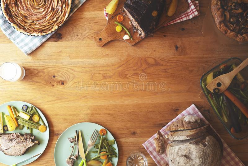 Pork steak with vegetables and apple pie on wooden table stock photo