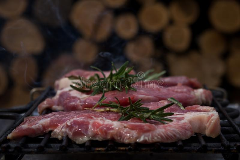 Pork Steaks With Rosemary Grilling on Hot Barbecue. Pork Steaks With Rosemary Grilling on a Hot Barbecue royalty free stock images